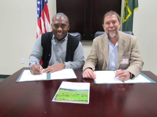 Barnie Gyant (Forest Service Deputy Regional Forester) and Mark Drew (Sierra Headwaters Program Director for California Trout) signing MOU agreement.