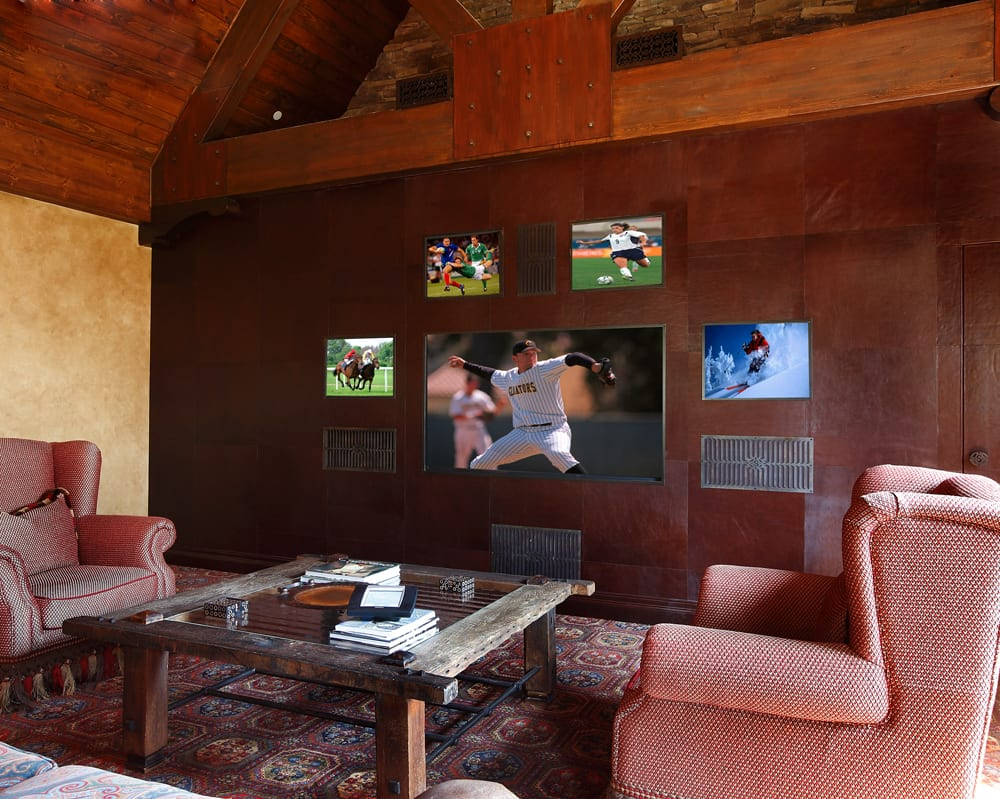Room set up for sports viewing with one large TV screen surrounded by several smaller screens