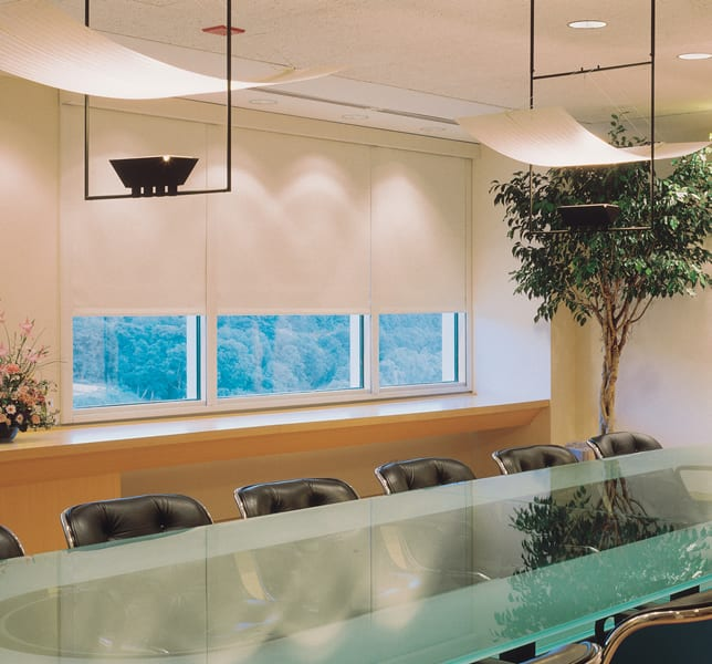 Conference room with black leather chairs, a glass table, and modern lighting