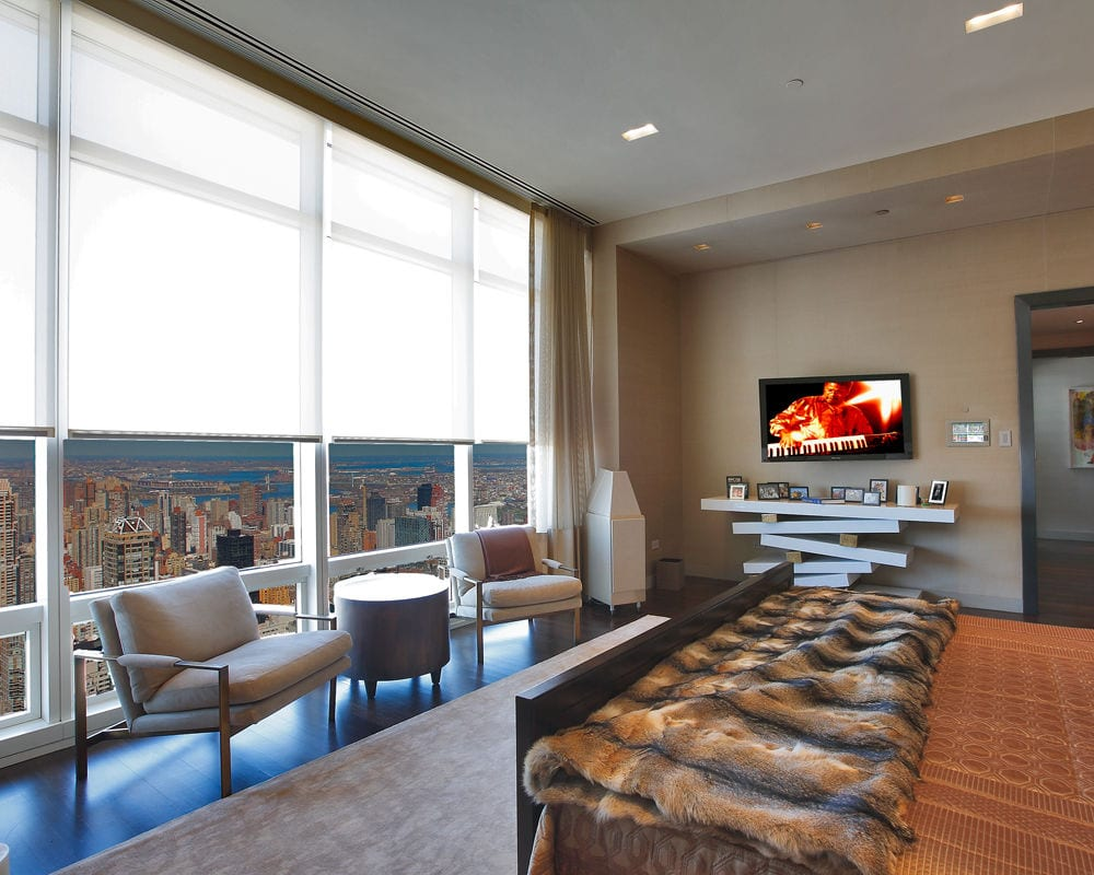 Image of a bedroom with a TV on one wall and large windows overlooking a city