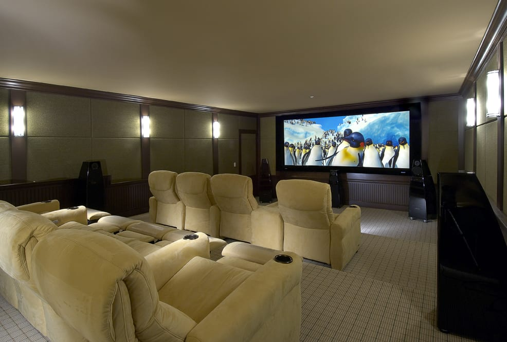 home theater room with tan recliner seating, a large flatscreen TV, and subwoofers